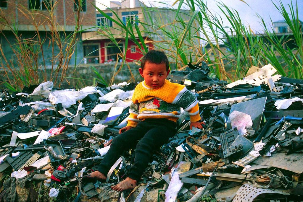 Child Sitting on Electronic Waste